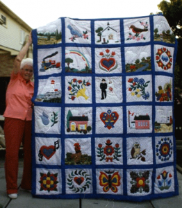 Mom holding up Bev and Kevin's quilt displaying all the panels