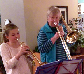 Lillian playing her trombone while her granddaughter plays a trumpet