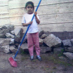 Here is 5-year-old Nancy who helps out at home by sweeping the floor.